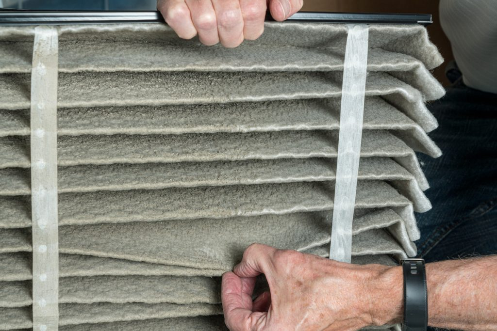 A hvac specialist looking at a dirty air filter of a Hvac furnace