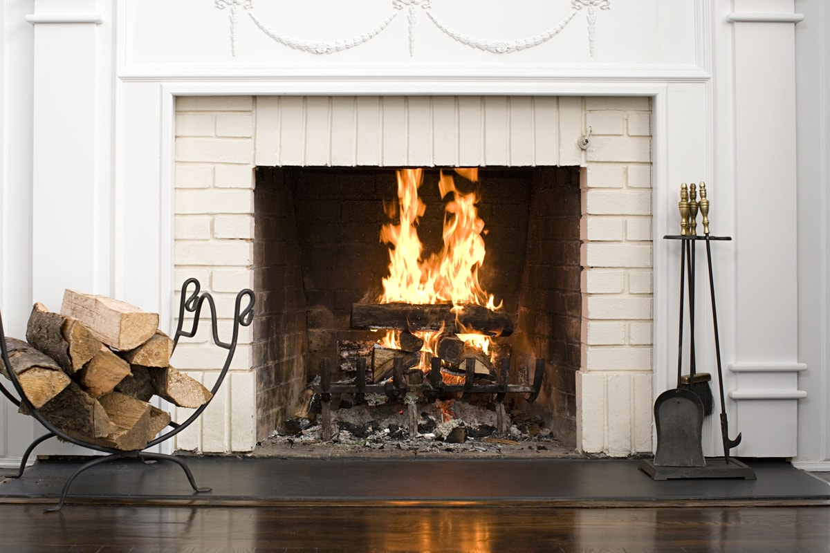 A gorgeous fireplace with a white colored mantel with firewood burning