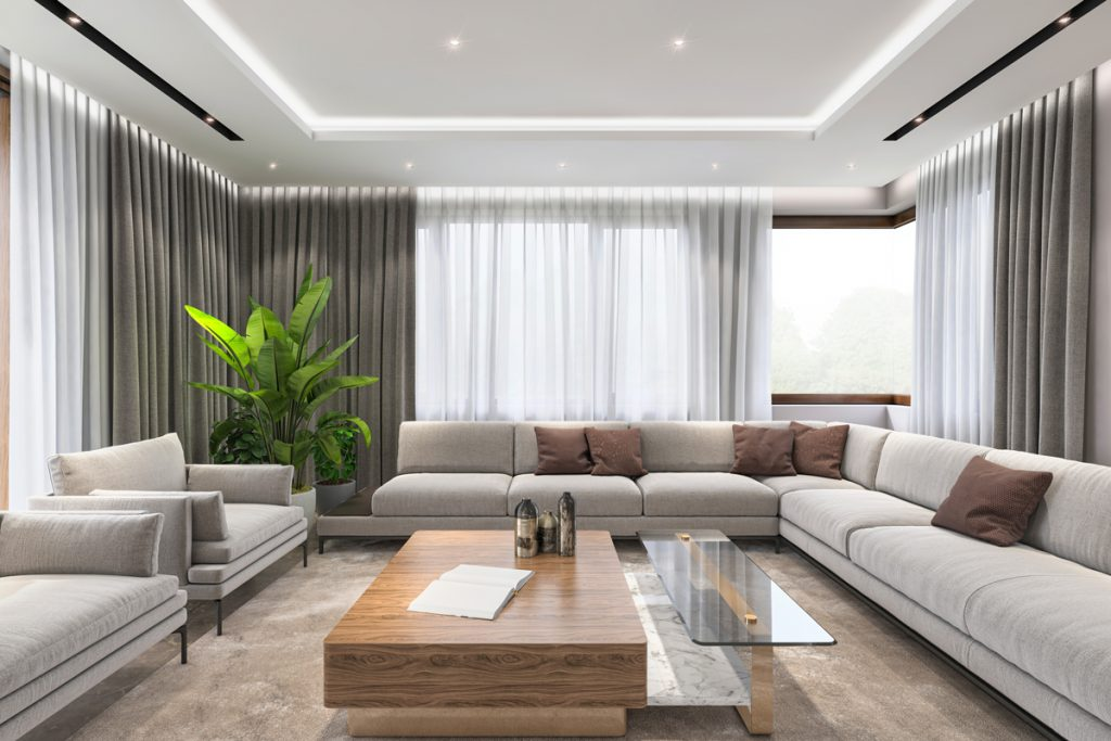 A modern luxury living room with gray and white curtains with a wooden table as a centerpiece