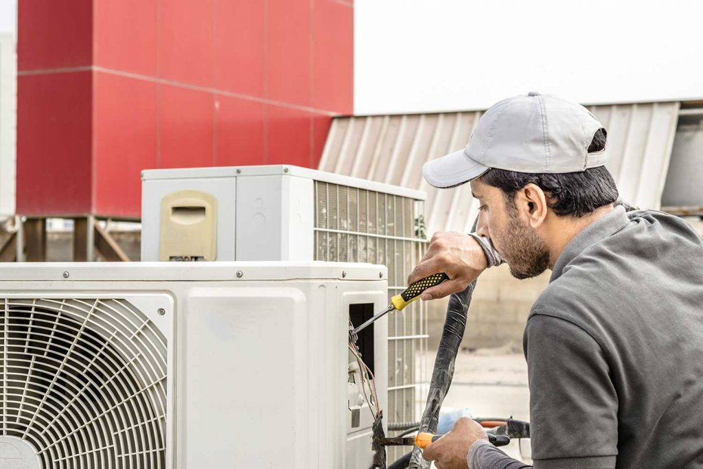 A professional repairman repairing a heavy duty central air conditioner unit at a rooftop