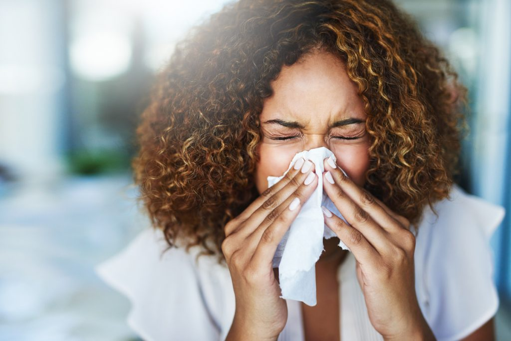 A woman sneezing and covering her nose with a tissue