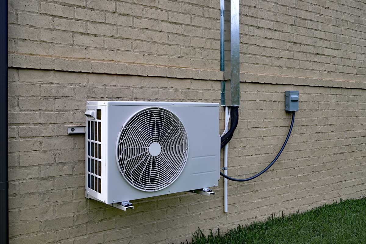 Air Conditioner mini split system next to home with painted brick wall, How Long Do Ductless Air Conditioners Last?