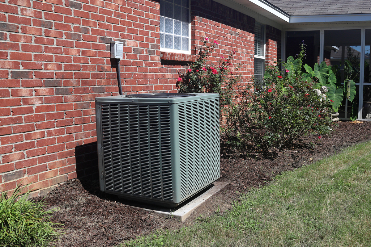 An Air conditioning condenser unit outside a brick walled house