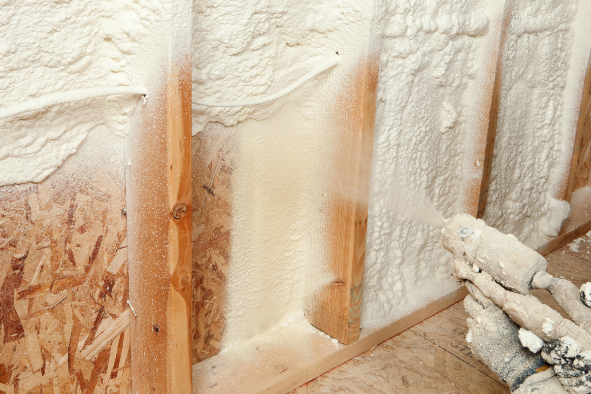 An insulation specialist spraying foam insulation to the wall