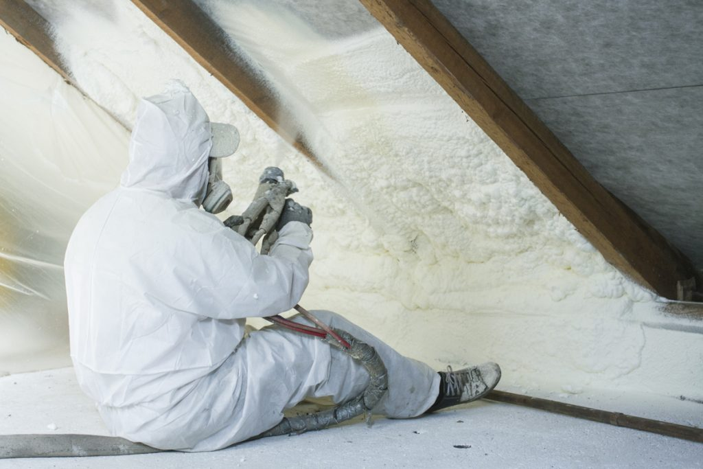 An insulation specialist using a sprayer to spray fiber glass insulation in the ceiling of the attic