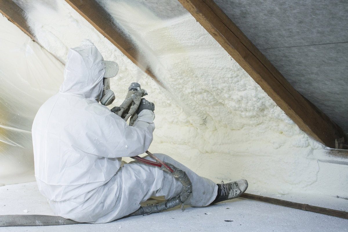 An insulation specialist with PPE on spraying foam insulation on the attic of the house, What Is The Best Insulation For Attics?