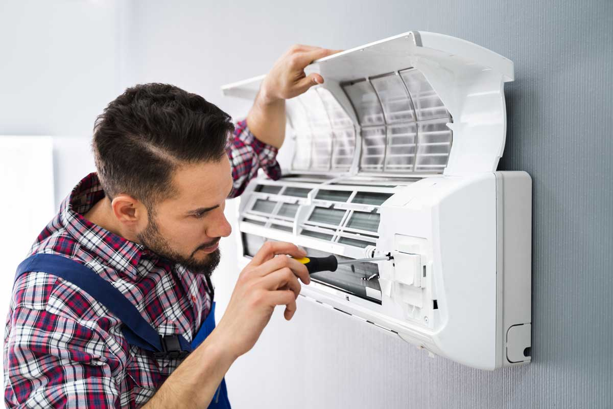 Happy Male Technician Repairing Air Conditioner With Screwdriver, Ductless Air Conditioning Not Cooling - What Could Be Wrong?