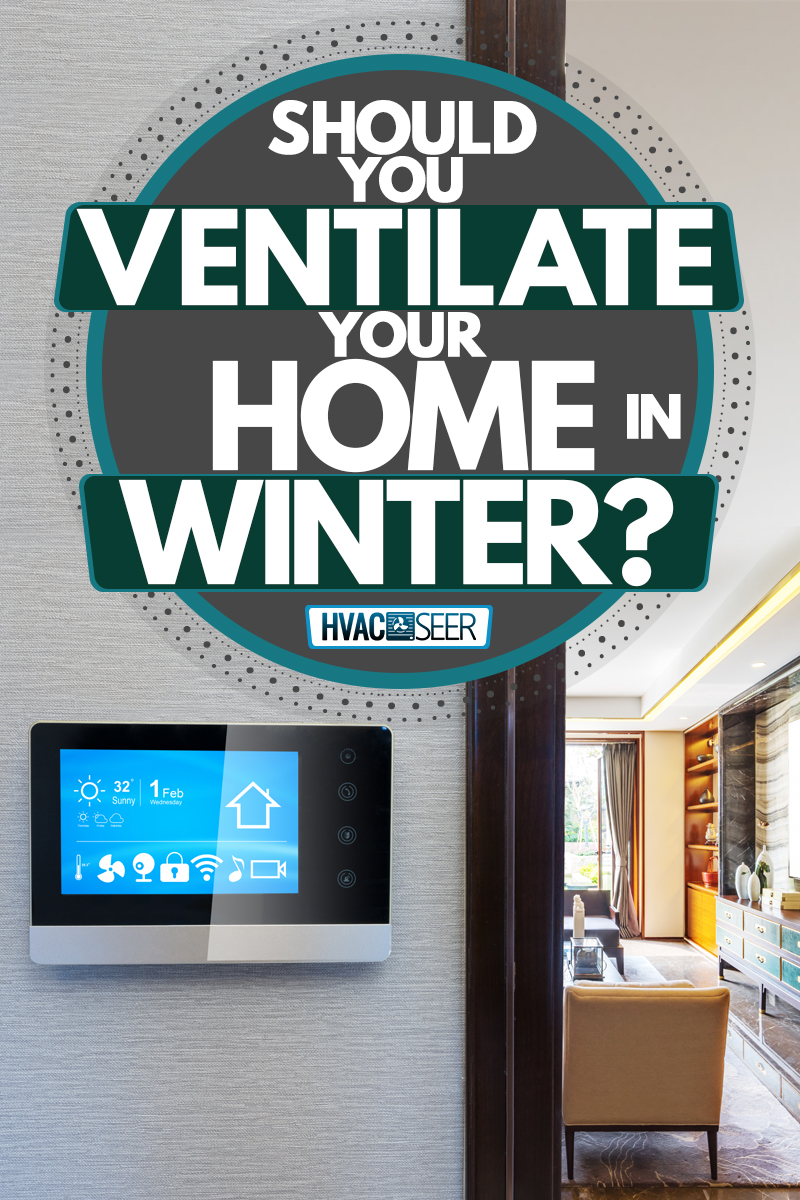 A touchscreen thermostat mounted on the wall and a modern living room on the background, Should You Ventilate Your Home in Winter?