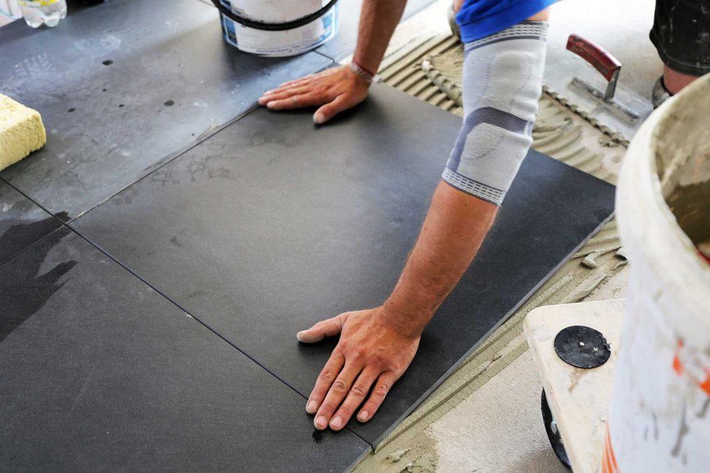Worker laying floor tiles