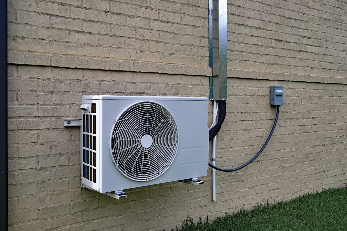 split type airconditioning condenser mounted on the wall with protected wiring