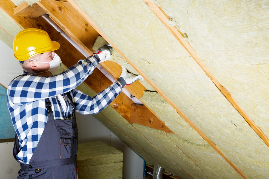 A man installing roof insulation layer over old insulation layer of attic
