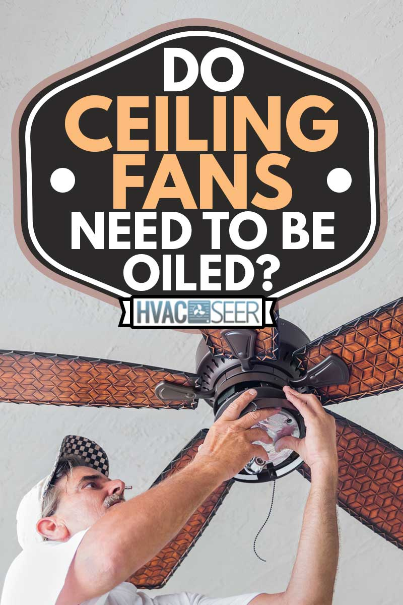 A man stands on a ladder while finishing hanging a ceiling fan, Do Ceiling Fans Need To Be Oiled?