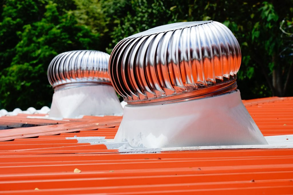 Two air ventilators spinning on a top of a roof