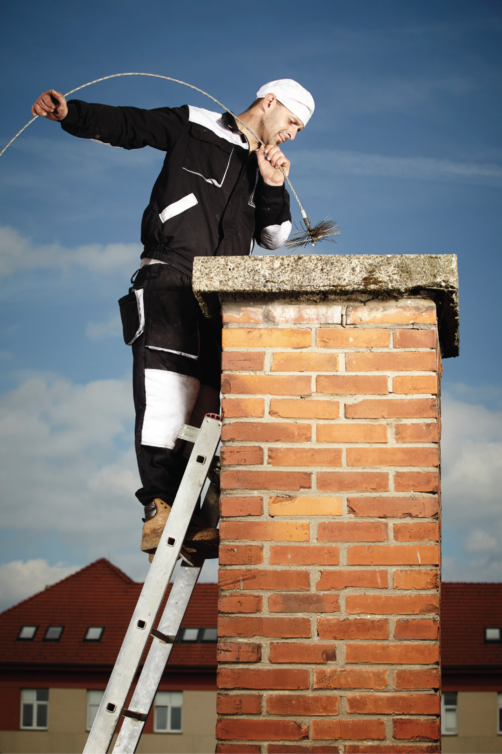 Chimney sweep man doing his job while on top of a ladder against a roof chimney