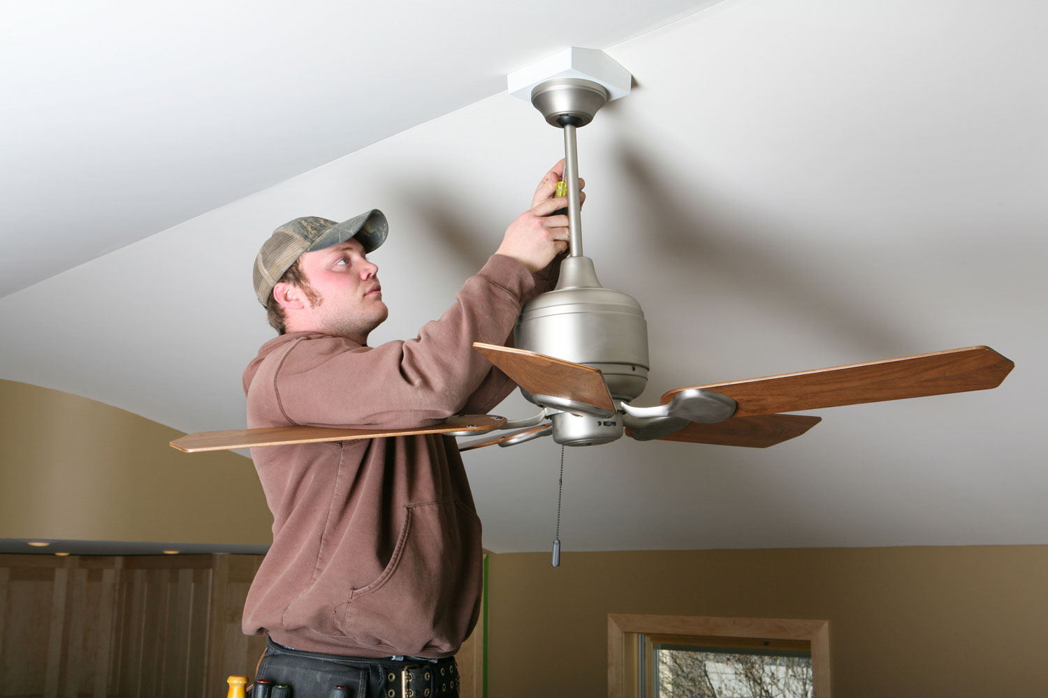 Electrician installing energy-saving ceiling fan on home addition job