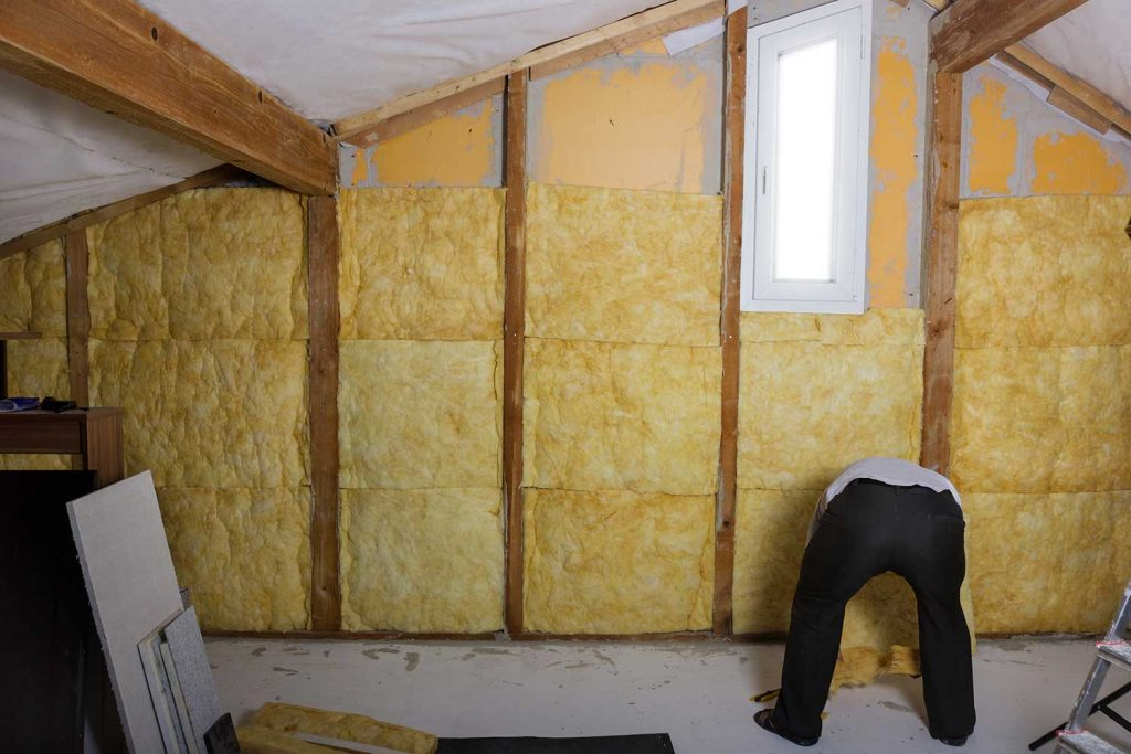 Handyman installing thermal insulation at the attic