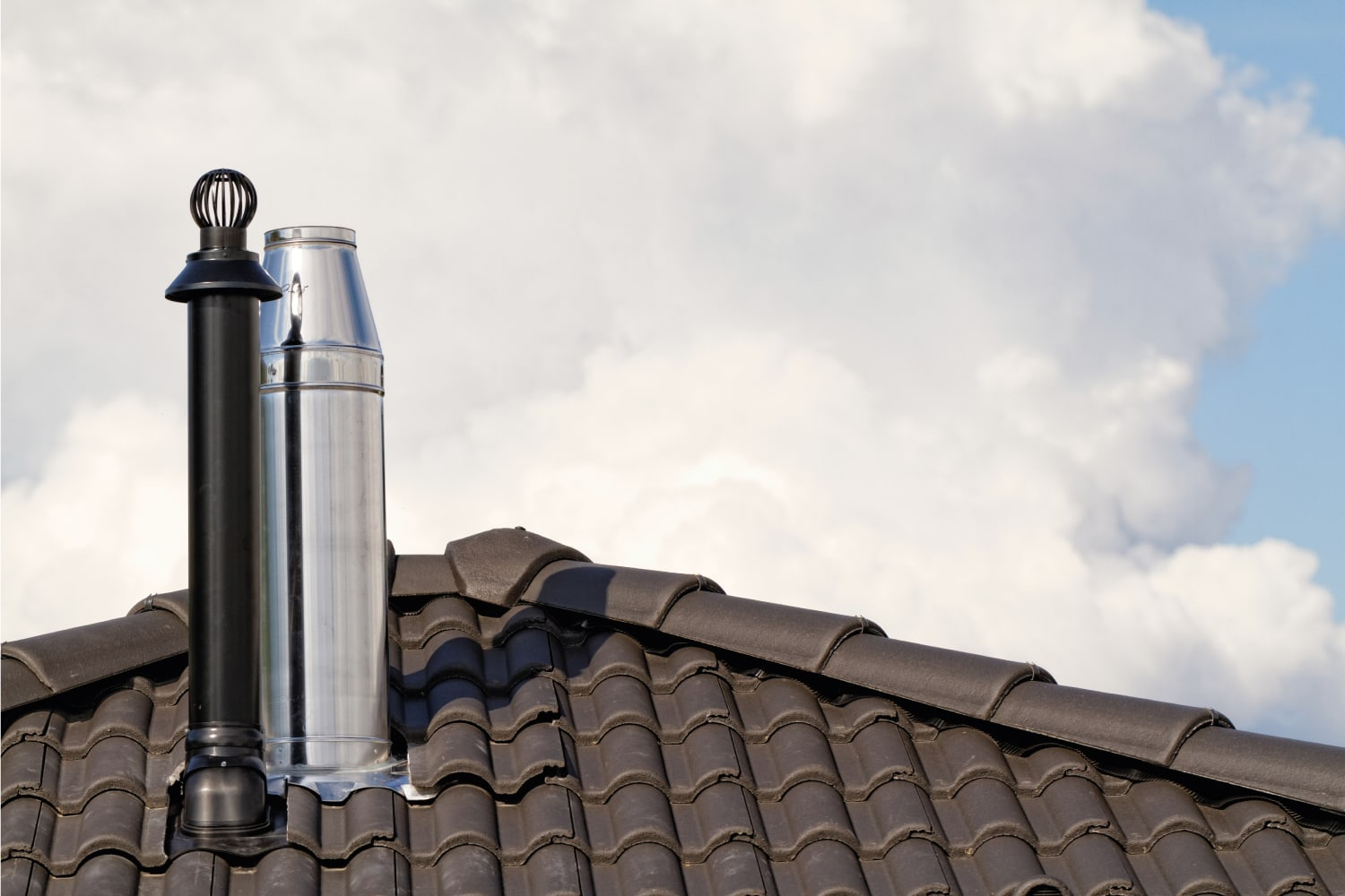 Modern draft increasing chimney cap on top of a house roof