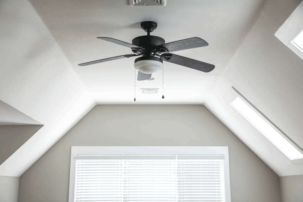 A small black ceiling fan inside a mansard bedroom