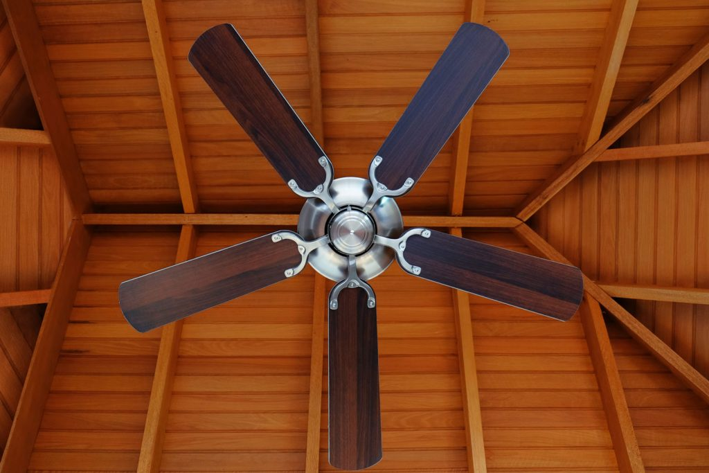 A modern wooden blade ceiling fan inside a rustic living room
