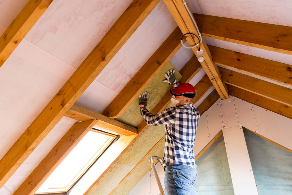 A worker installing roof insulation on the attic of a house under construction