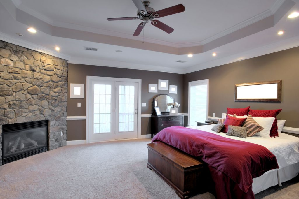 Interior of a spacious contemporary living room with red velvet beddings, carpeted flooring, and a ceiling fan on the center