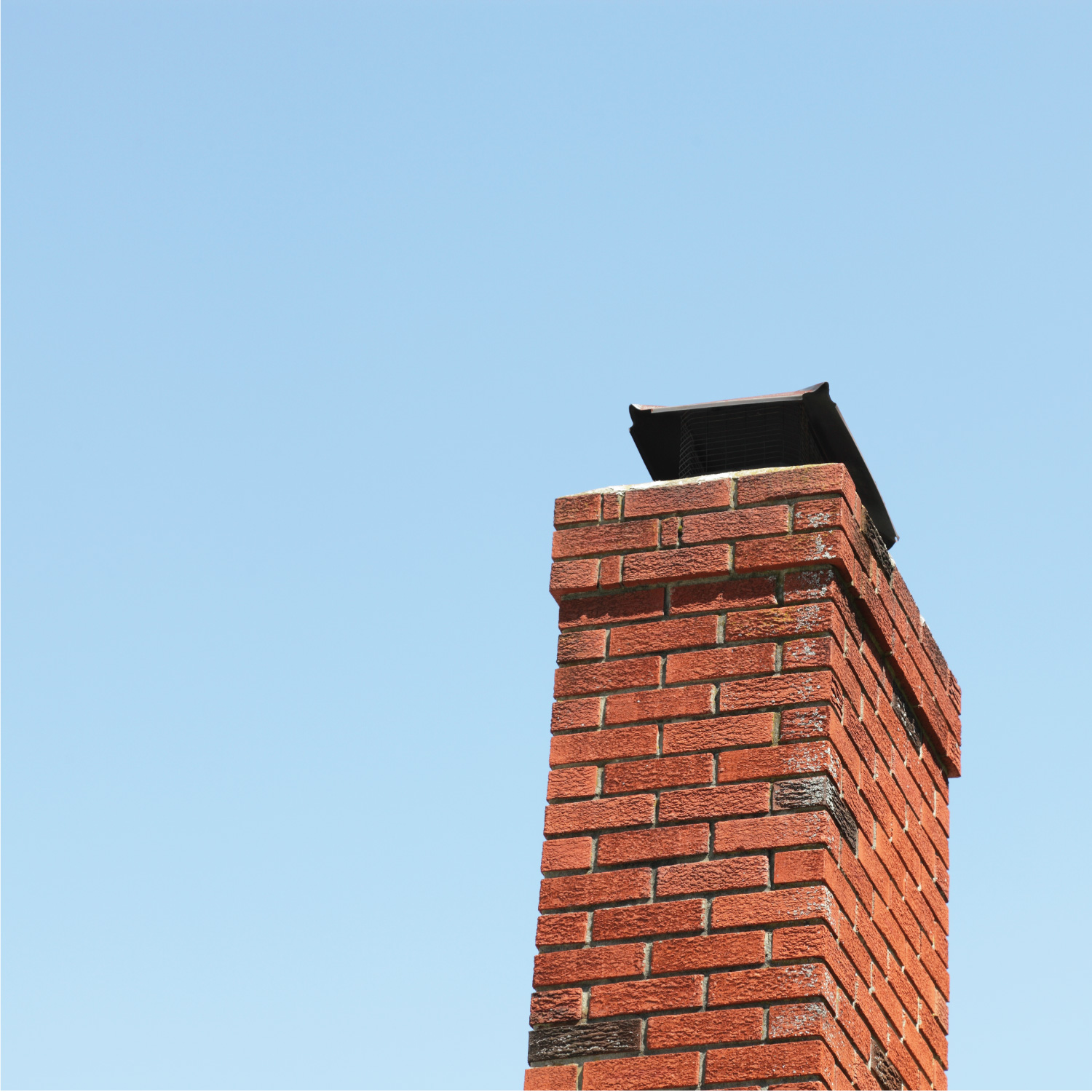 A red brick chimney with a capped metal grate on top to prevent rain, birds and pests from entering against a blue sky