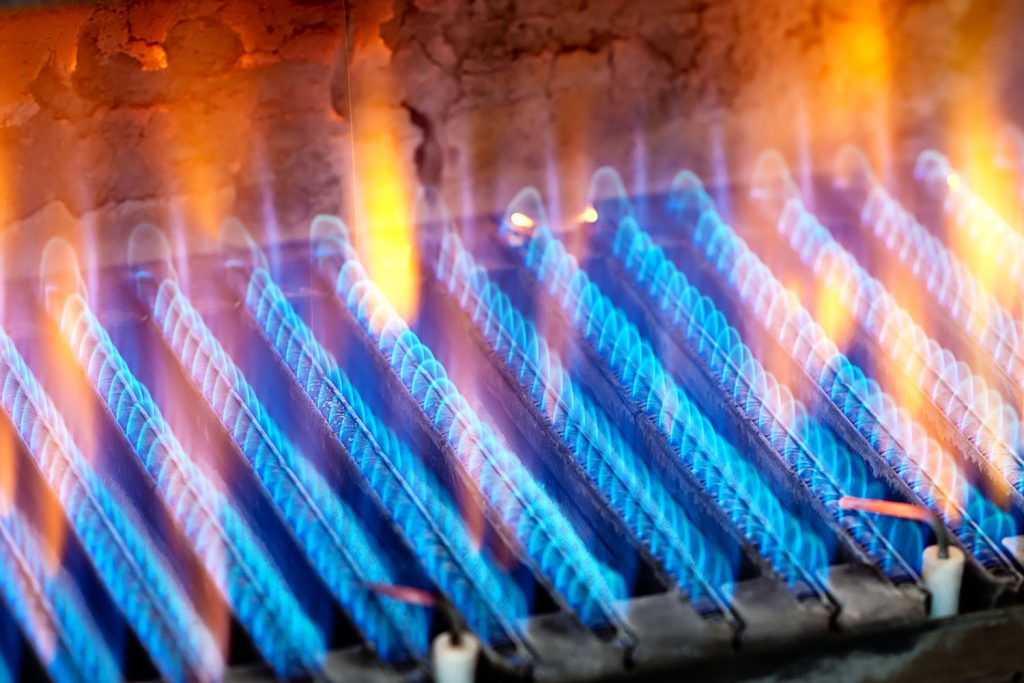 A gas burner turned on blowing hot blue flame