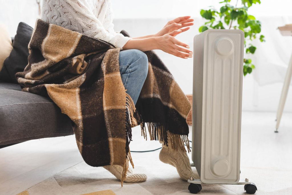 A woman wearing a scarf and sitting next to the heater