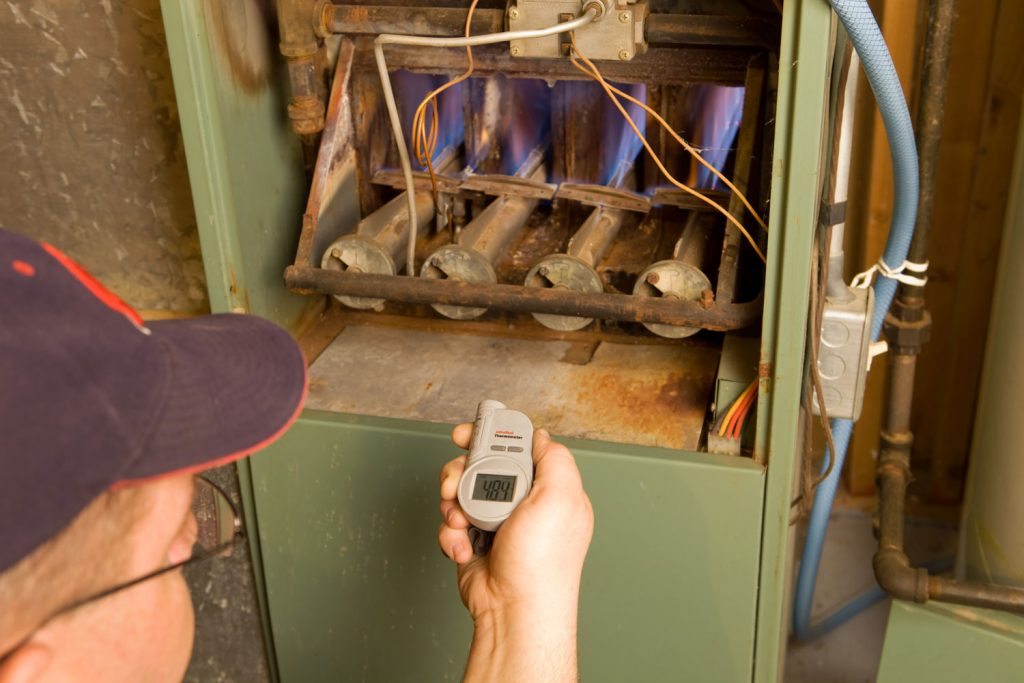 A man measuring the temperature of the gas furnace