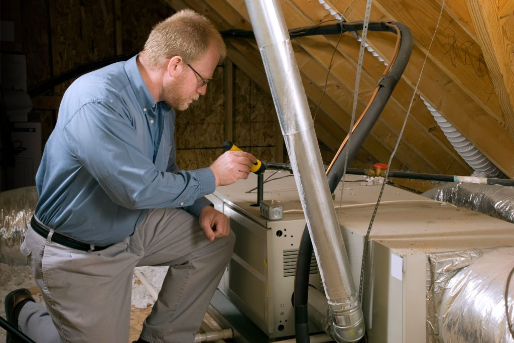 A repair man checking the furnace in the attic, Can You Put A Furnace In The Attic?