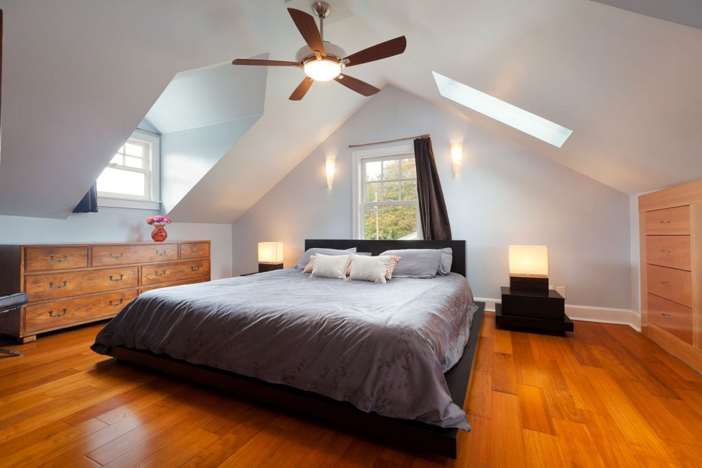 Interior of a rustic inspired mansard bedroom with a gray bed, wooden cabinet, and wooden flooring