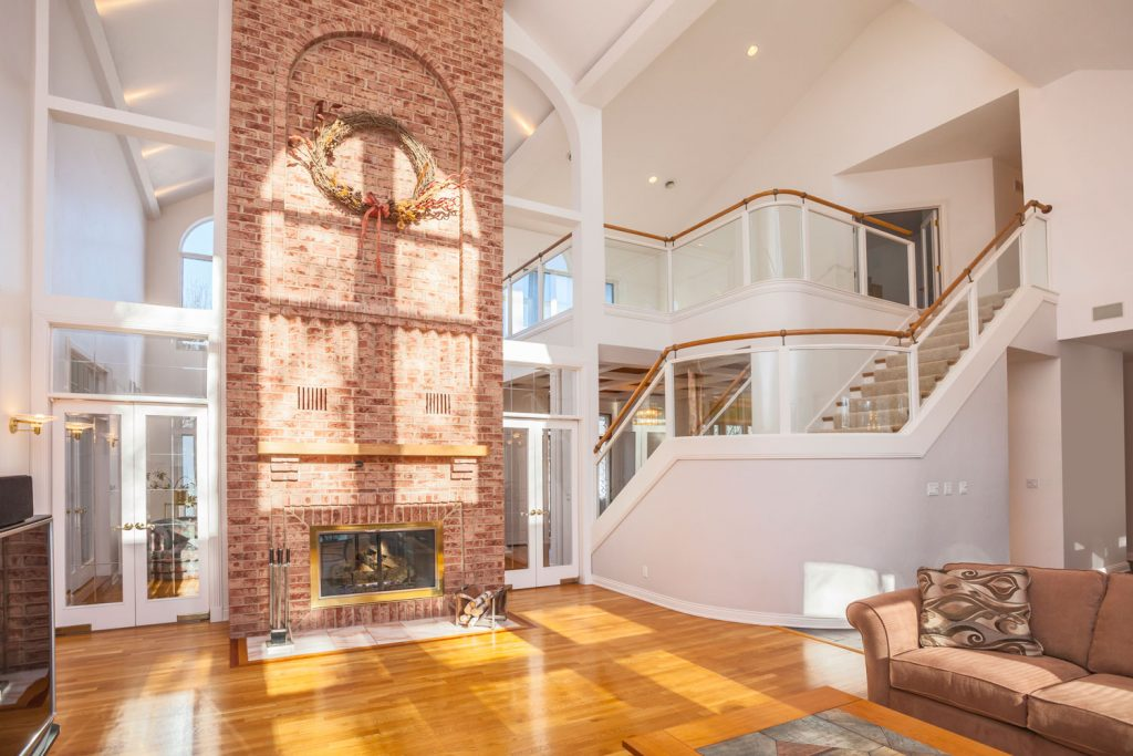 A huge contemporary living room with a cathedral ceiling brickstone fireplace, and a polished wooden flooring, Do Cathedral Ceilings Need Ventilation?