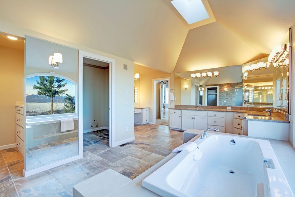A lovely interior of a modern contemporary and bathroom with white white bathtub, and a huge glass door shower area