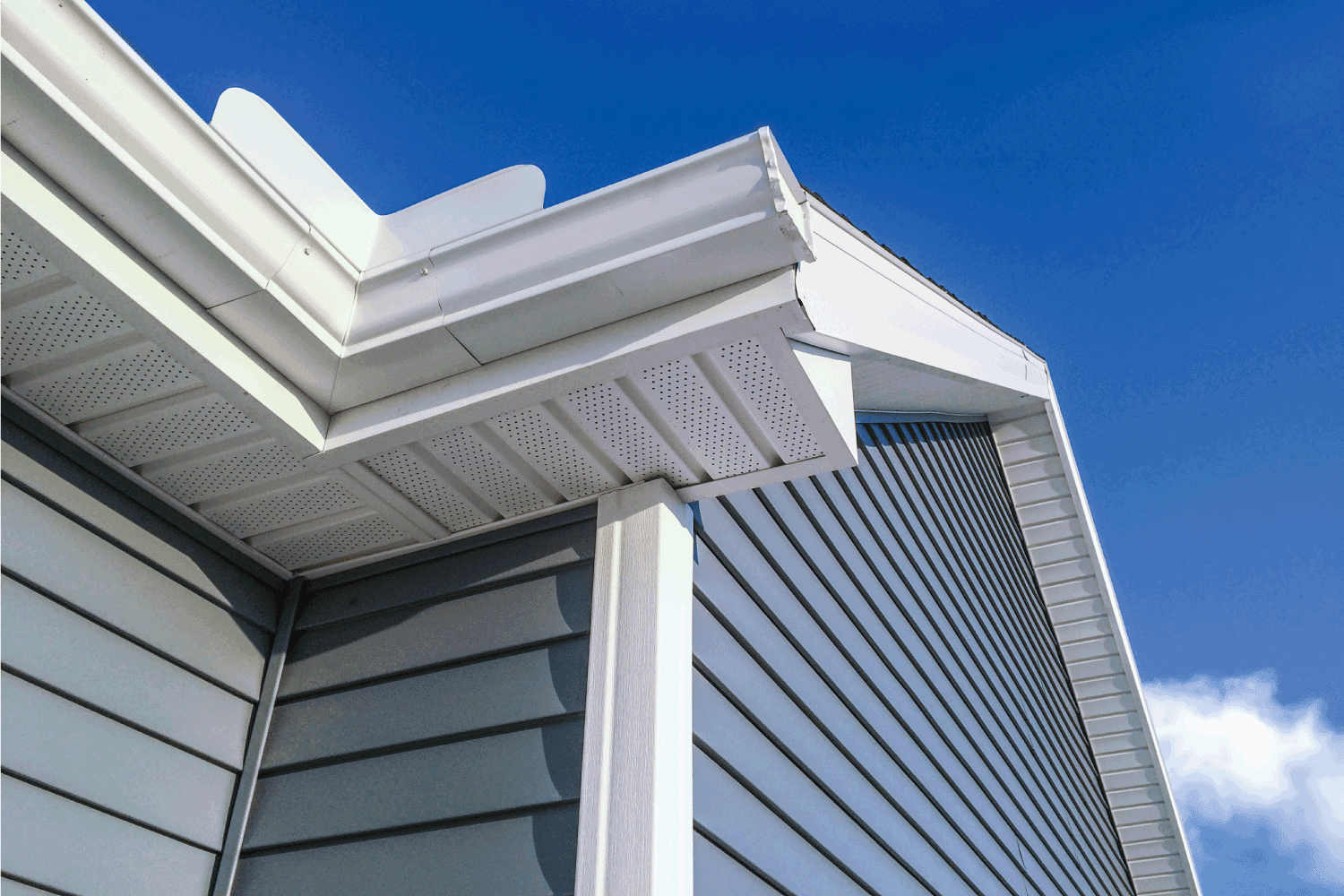 A low angle view of soffit, gutters, downspout and vinyl siding on a new home. Blue sky is in the background.