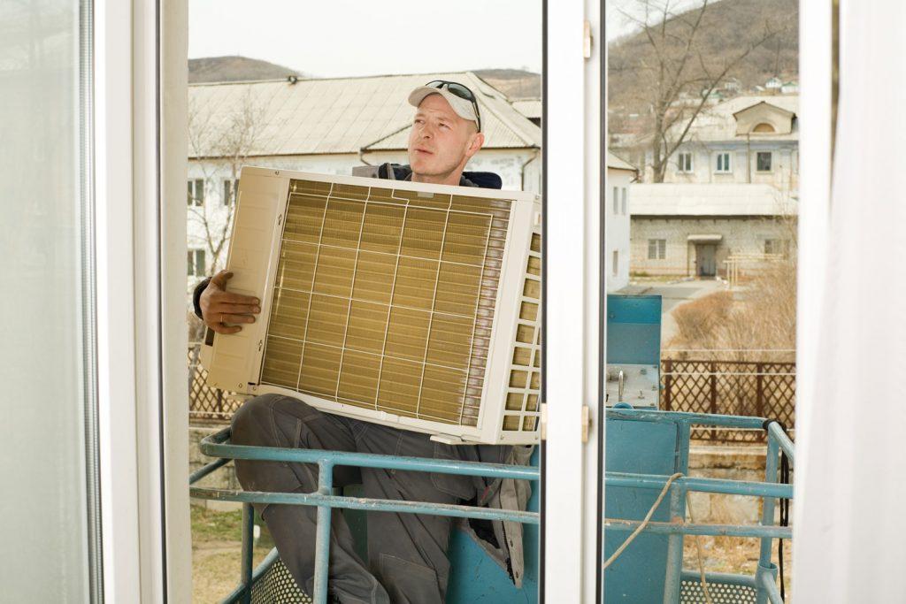 A HVAC repair personnel installing an air conditioner