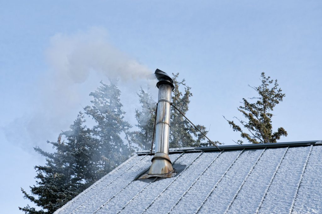 A smoking chimney on top of the roof of a house with snow