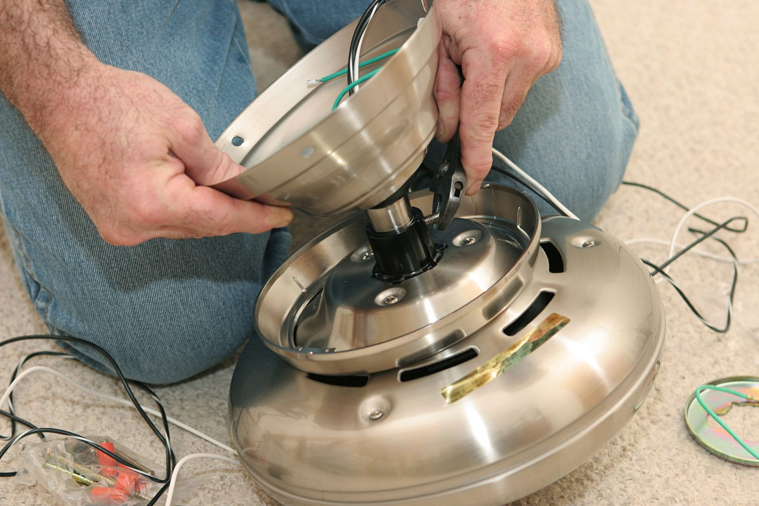An electrician assembling a ceiling fan motor. All work is being performed by a licensed master electrician according to National Electric Code standards