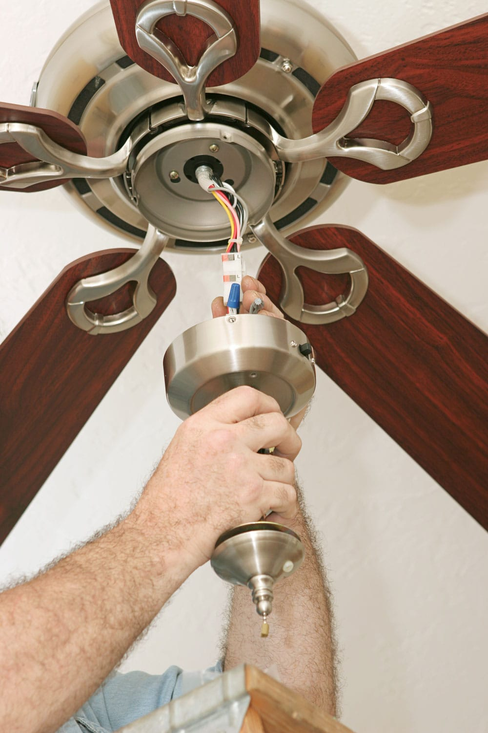 An electrician wiring up a ceiling fan. All work is being performed to code by a licensed master electrician