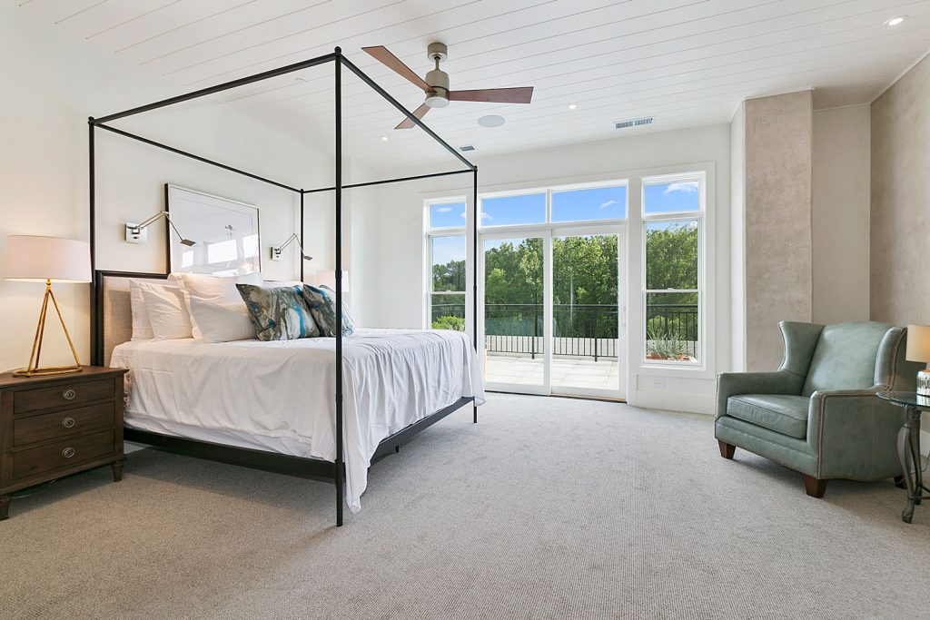 Elegant teal colored bedroom with white beddings and mint colored furnitures with gray carpeted flooring