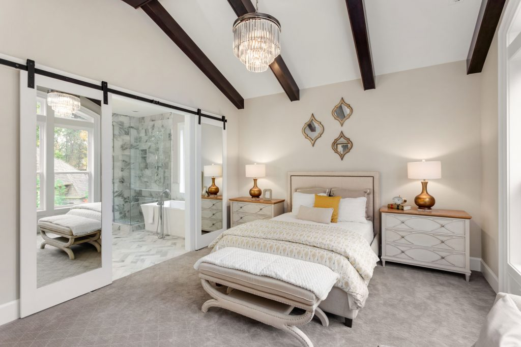 Luxury masters bedroom with white cabinetry and a gray carpeted flooring