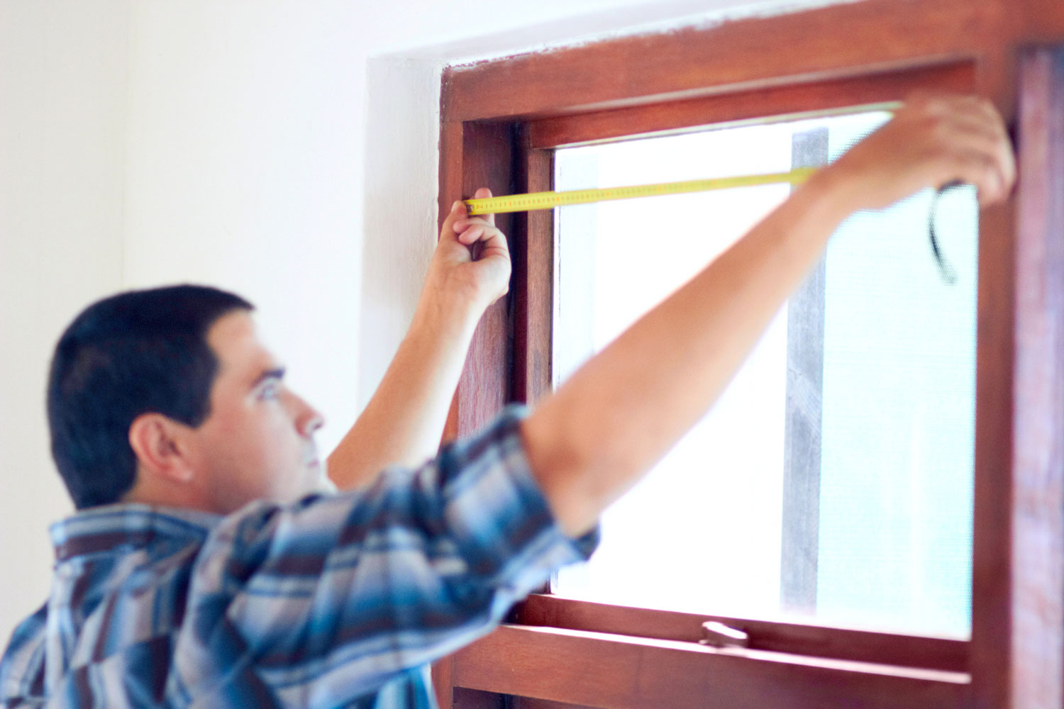 Shot of a middle aged handy man measuring a window
