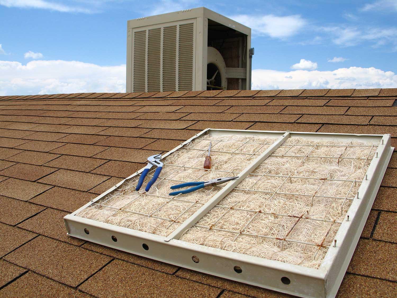 Swamp cooler maintenance on reddish shingled roof