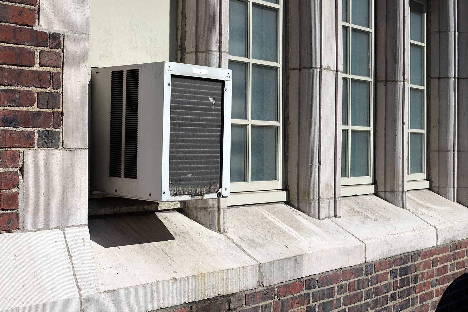Window air conditioner unit on old brick building