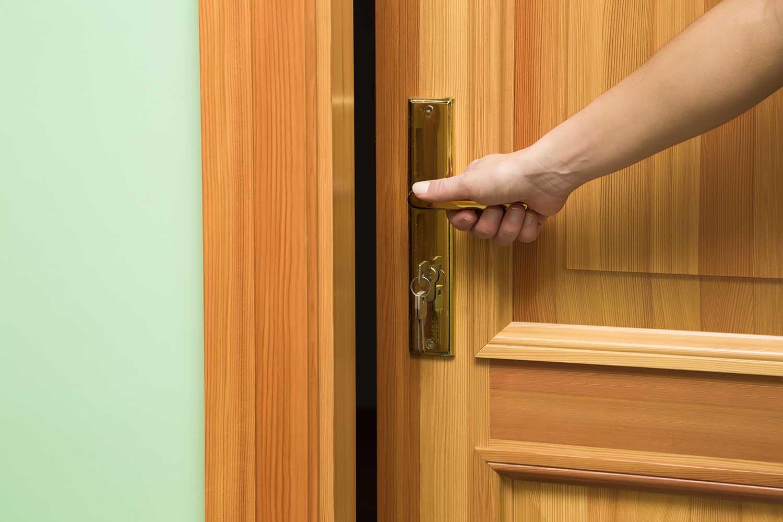 Woman's hand opening the wooden door