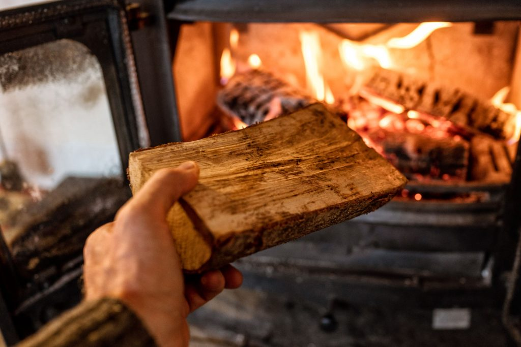 A man throwing a block of wood to the wood stove