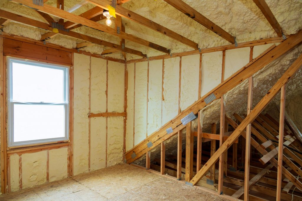 A room at a newly constructed home is sprayed with liquid insulating foam, How To Insulate Existing Interior Walls