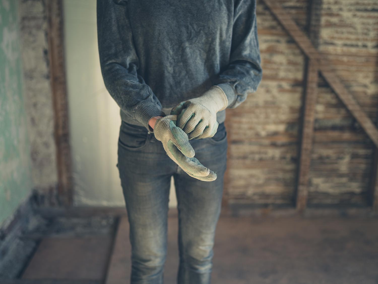 A young worker standing in a loft undergoing renovations and is putting on a pair of gloves