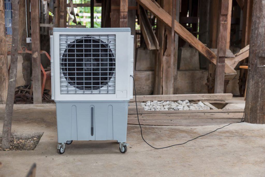 An evaporative air cooler inside the attic of a house