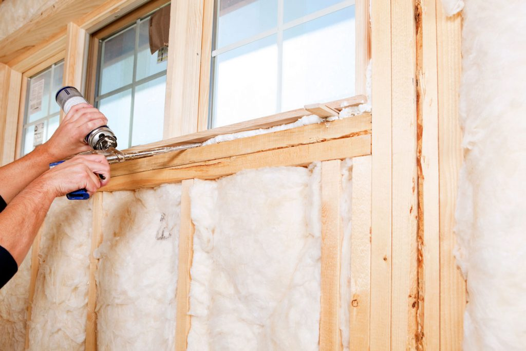 Construction Worker Applying Expandable Foam Insulation to Window, Does Foam Insulation Shrink Over Time?