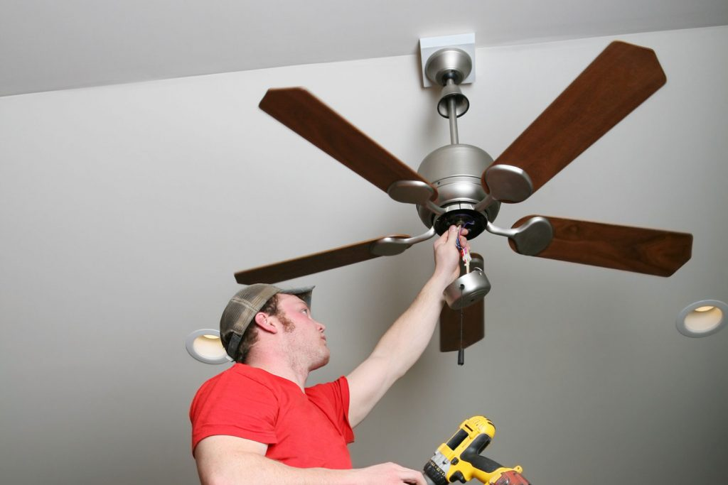 Electrician installing energy-saving ceiling fan on home addition job, How To Install A Ceiling Fan On A Sloped Ceiling